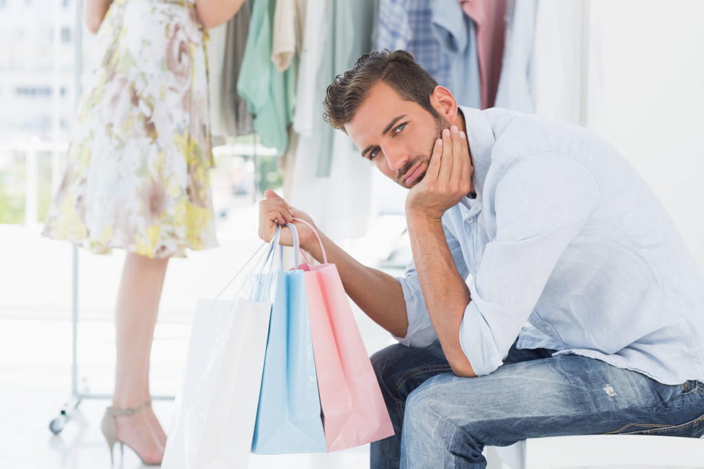 man-with-shopping-bag-bored-while-woman-searches-clothes-rack